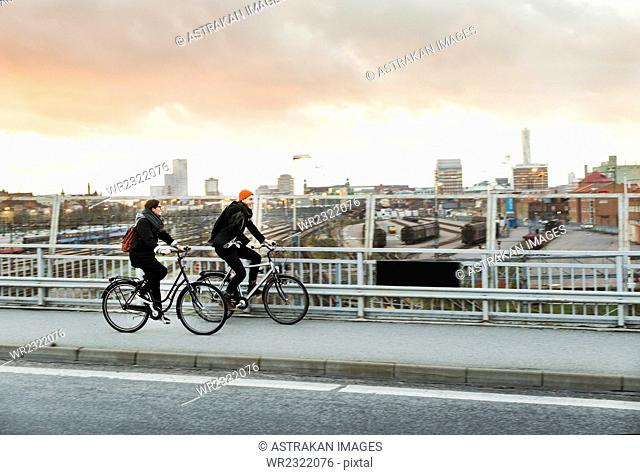 Side view of man and woman riding bicycles on bridge in city