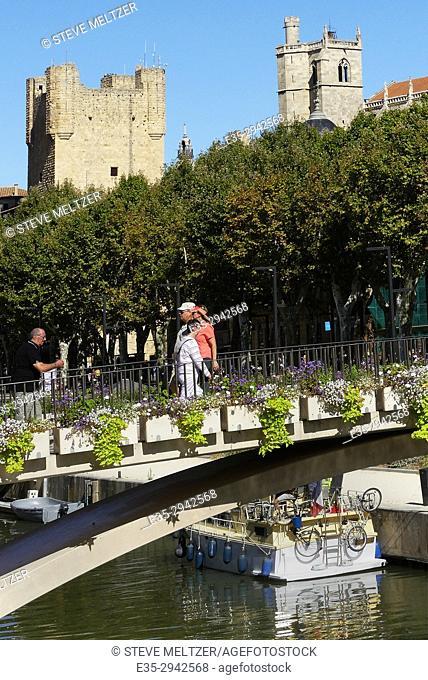 Pedestrians crossing a foot bridge over the Canal de la Robine, Narbonne, France