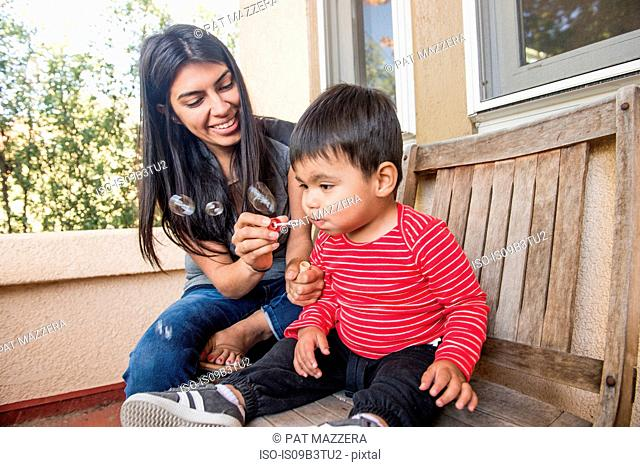 Male toddler with mother concentrating on blowing bubbles on porch bench