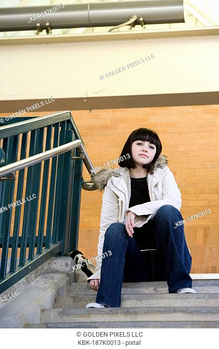 Portrait of a young woman sitting at the top of a concrete staircase