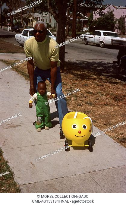 Scene of an African American man helping an African American toddler to stand on the sidewalk in a residential neighborhood of Los Angeles, California, 1976