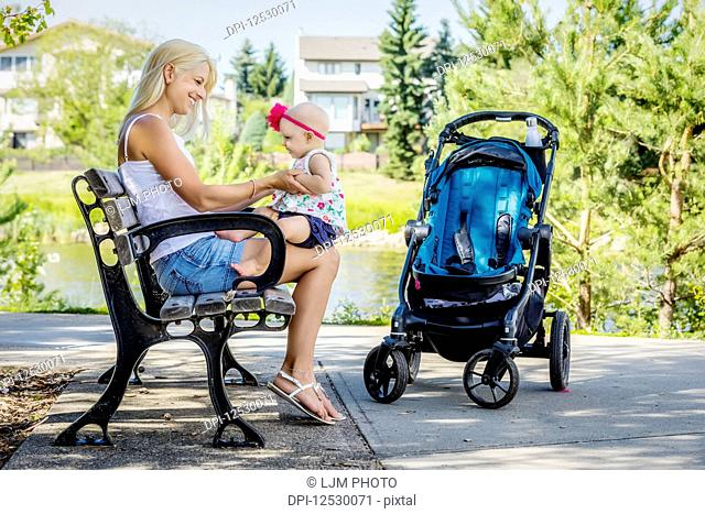 A beautiful young mother holding her baby daughter on her knees while resting on a park bench beside the lake after walking with a stroller on a warm sunny day;...