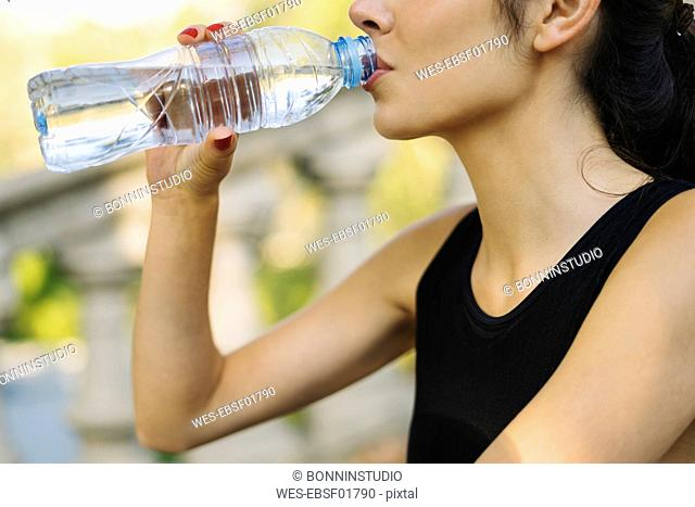 Close-up of sportive young woman drinking from bottle
