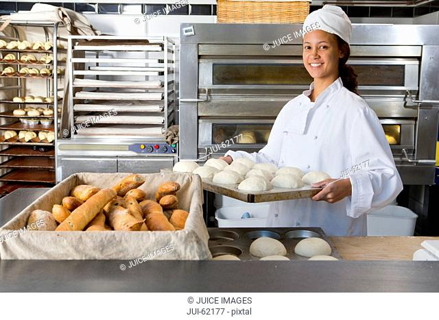Smiling baker carrying bread in bakery kitchen