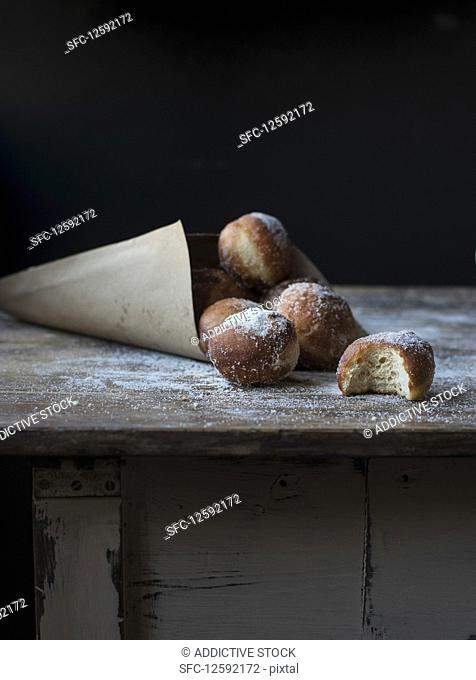 Fresh beignets near set of baked loaf in craft paper with powdered sugar