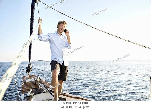 Portrait of smiling mature man on the phone on his sailing boat