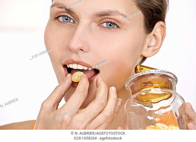 Woman eating honey sweets for sore throat