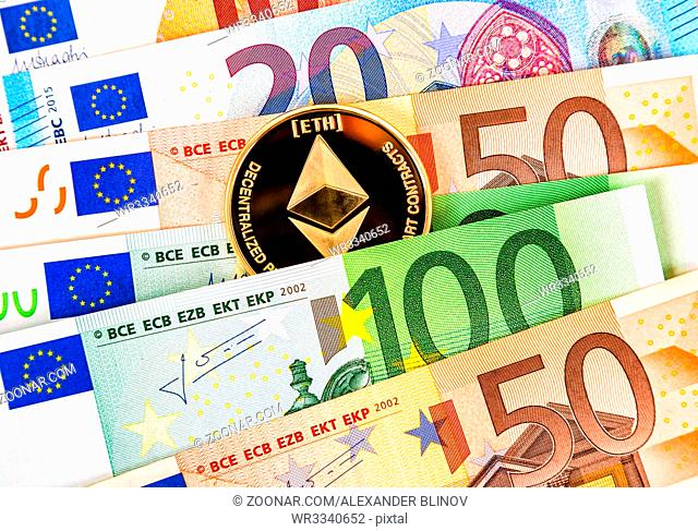 Digital cryptocurrency coin Ethereum lying on the euro banknotes. Business concept of virtual money