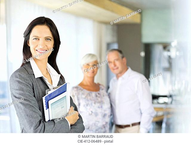 Financial advisor holding folders and tablet computer