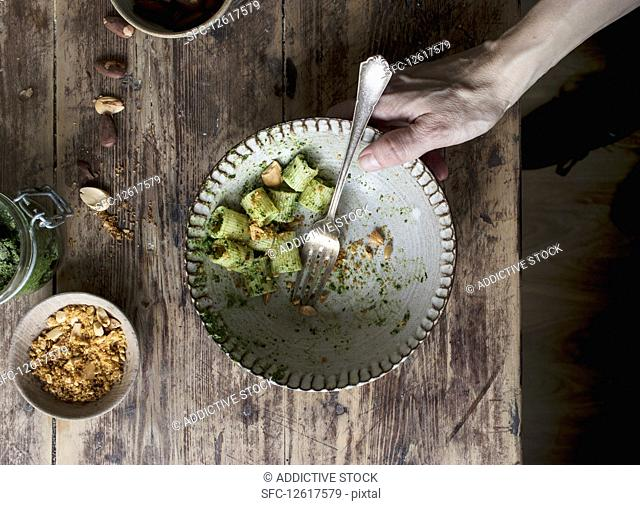 Hands taking bowl of delicious pasta paccheri with tasty kale pesto and ground peanuts