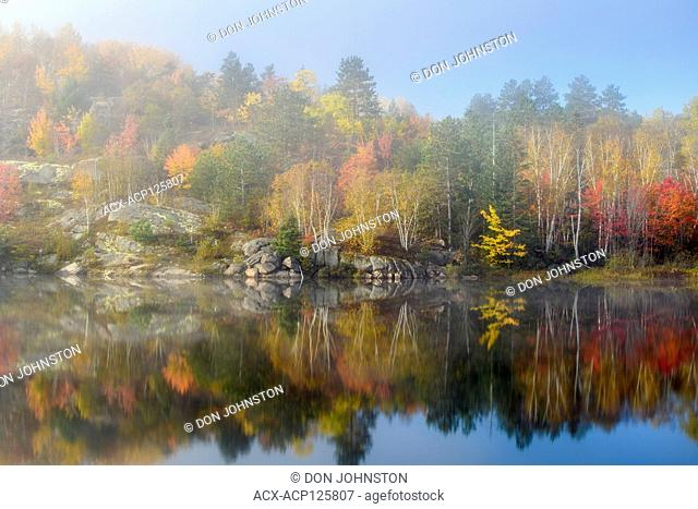 Autumn reflections in Elbow Lake with lifting fog, Greater Sudbury, Ontario, Canada