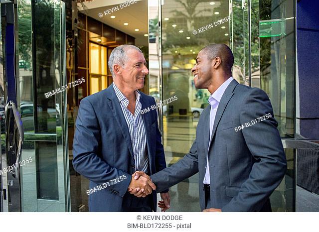 Businessmen shaking hands at office building