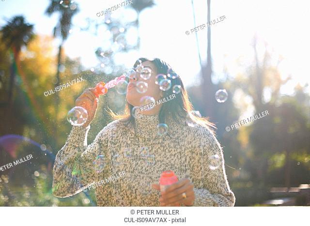 Mature woman blowing bubbles, Seville, Spain