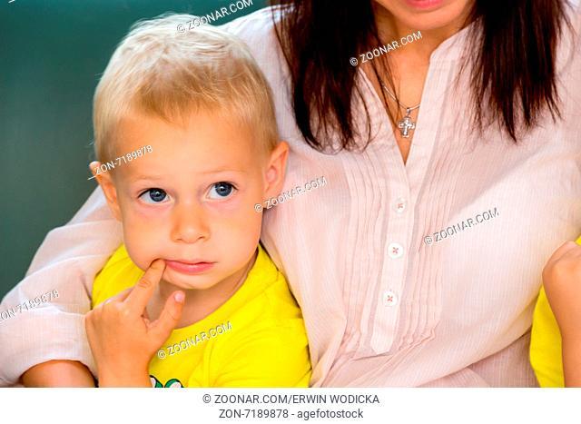 Ein junge lehnt nachdenklich an der Schulter seiner Mutter