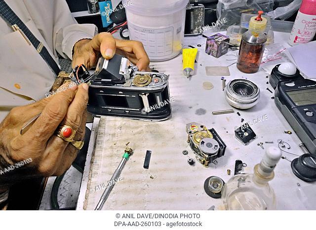 man repairing film camera, India, Asia