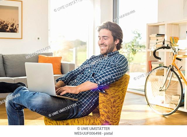Portrait of smiling young man sitting on armchair in the living room using laptop