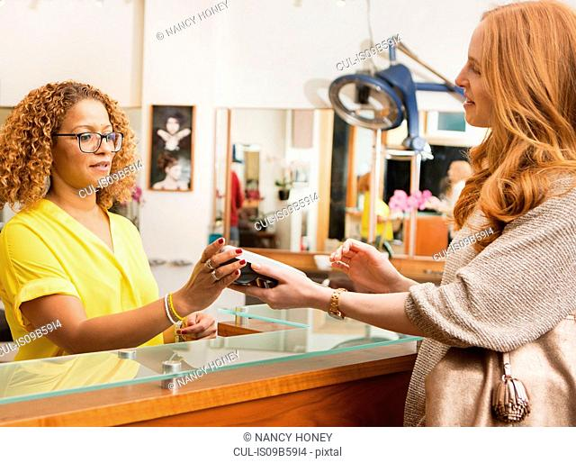 Female customer paying with credit card reader in hair salon