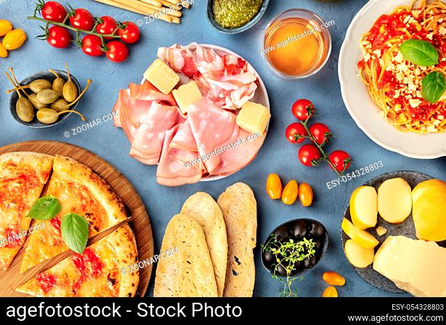 Italian food. Pizza, pasta, cheese, ham, capers, wine, tomatoes, olives and bread, shot from the top