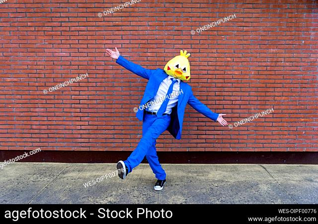 Man wearing vibrant blue suit and bird mask posing on one leg in front of brick wall