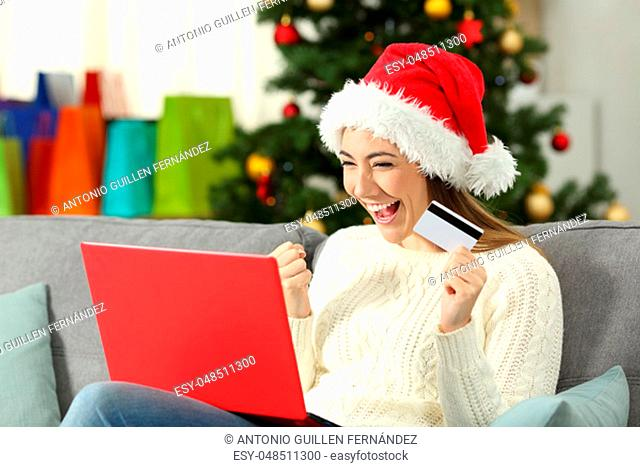 Excited girl holding a card shopping online on christmas