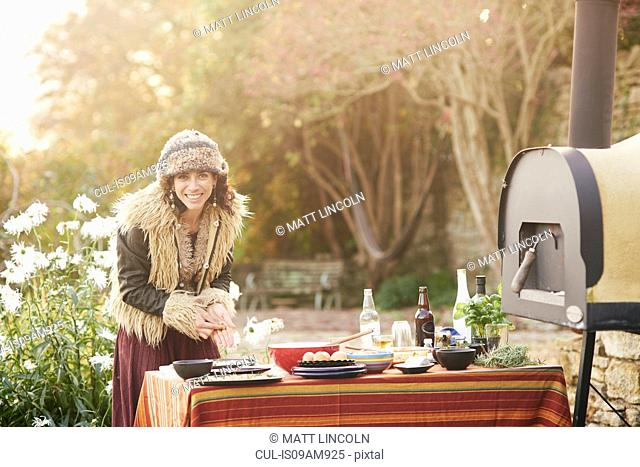 Mature hippy female preparing food on garden table