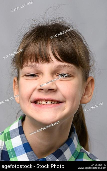 Portrait of a funny smiling ten-year-old girl of European appearance, close-up