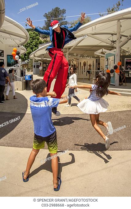 A costumed stilt walker shares a jump with an exuberant Asian American brother and sister at an art festival in Laguna Beach, CA
