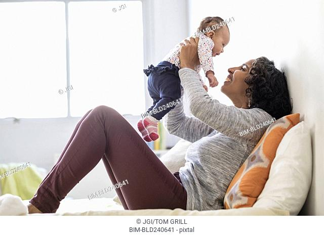 Hispanic mother playing with baby daughter on bed