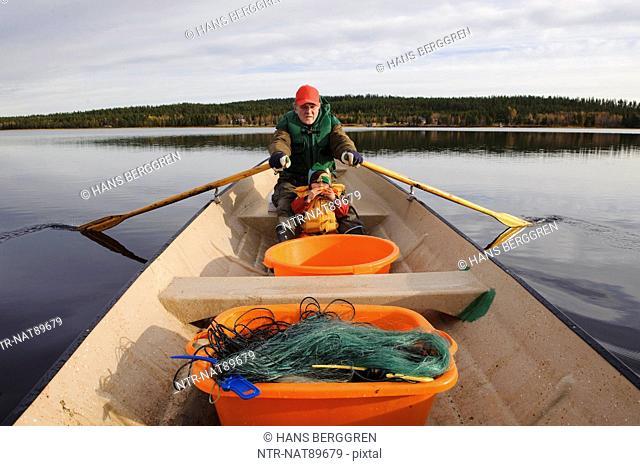 Senior fisherman with grandson rowing