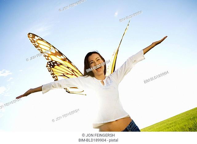 Asian woman with butterfly standing with arms outstretched