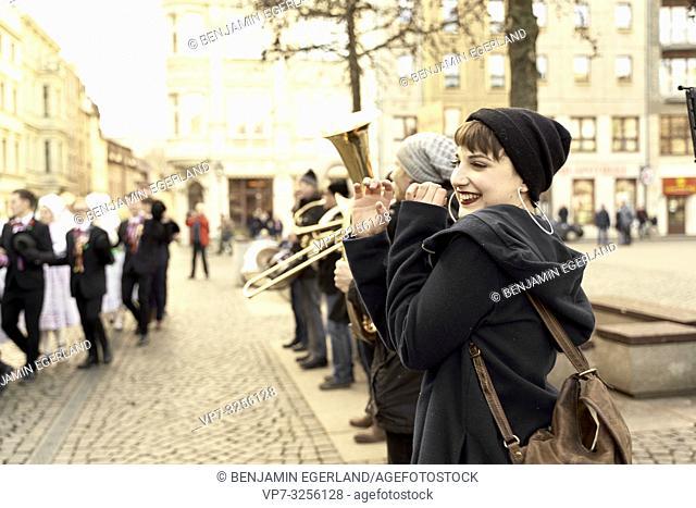 woman emulating trumpeter musicians at German culture event, humorous joking, in city Cottbus, Brandenburg, Germany