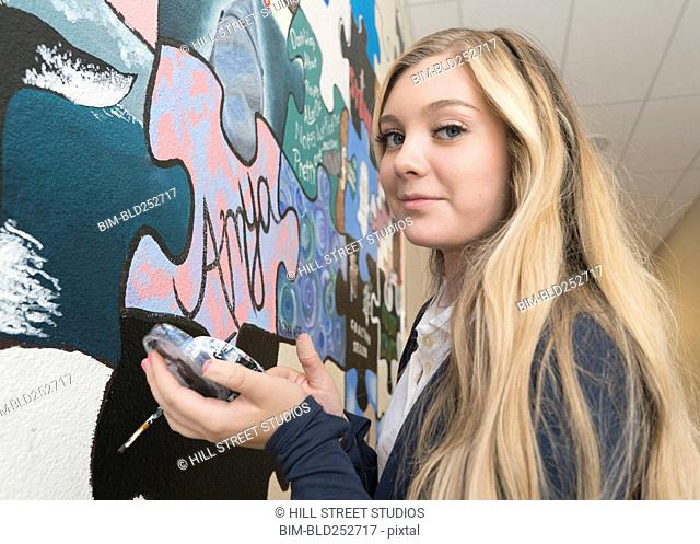 Portrait of Caucasian girl mixing paint for wall mural in school