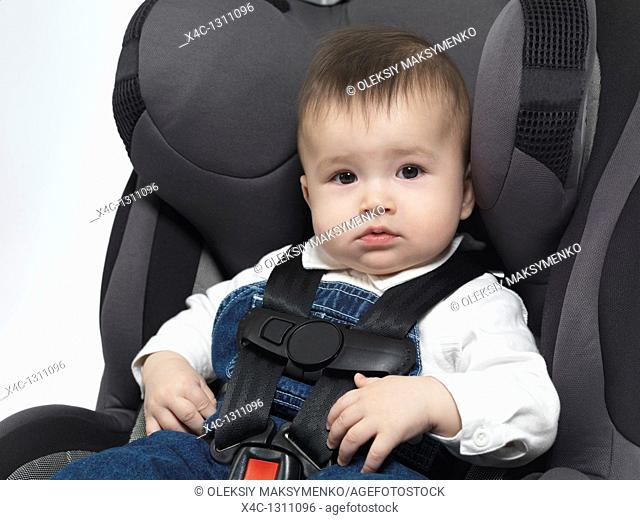 Seven month old baby sitting in a booster seat