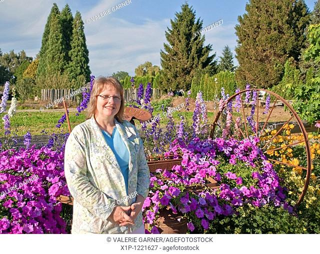 This smiling Caucasian middle aged woman has rustic farm equipment in the background of this rural, floral stock photo Flowers are larkspur and petunias mainly...
