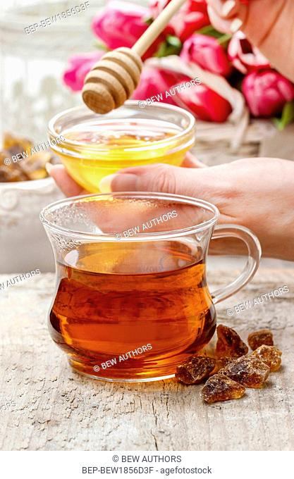 Cup of golden tea served with honey