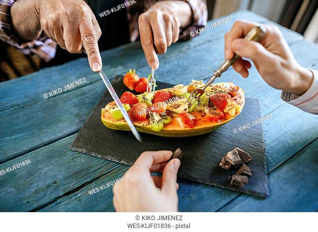 Close-up of hands of man and woman eating papaya with kiwi, banana and strawberries
