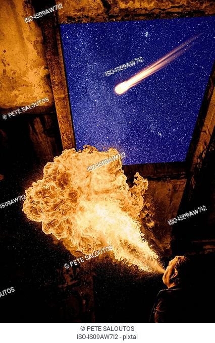 Low angle view of man fire breathing, meteor in starry night sky