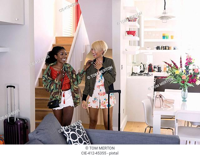 Excited young women friends arriving at house rental