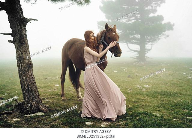 Caucasian woman petting horse