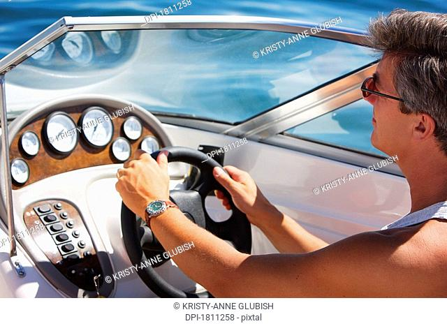 A man driving a speed boat