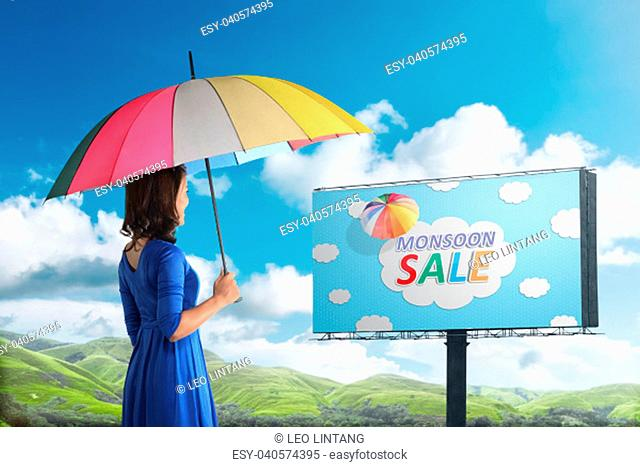 Happy asian woman looking at monsoon sale sign on billboard. Monsoon sale concept