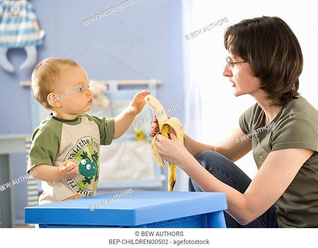 Mother giving banana to her little son