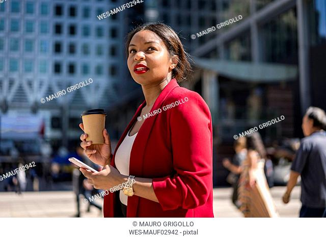 Portrait of businesswoman with coffee to go and cell phone, London, UK