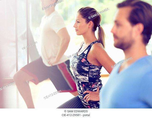 Focused woman lunging in exercise class