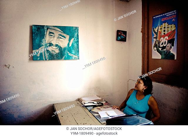 A Cuban office worker watching a painted portrait of the Cuban Revolutionary leader Fidel Castro, hung on the wall of the Cuban state office in Santiago de Cuba