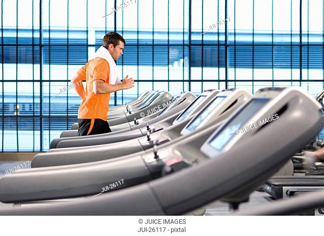 Man running on treadmill with towel around neck in health club
