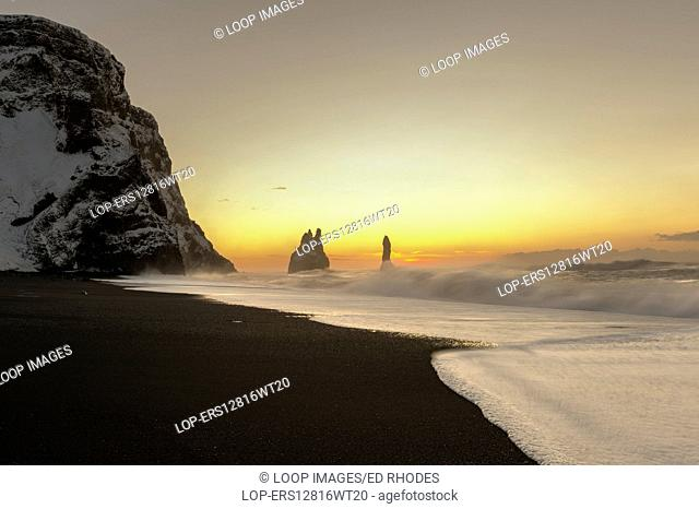 The Reynisdrangar basalt sea stacks and the Reynisfjara black sand beach at sunrise