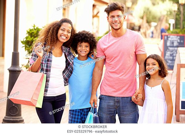 Portrait Of Family Walking Along Street With Shopping Bags