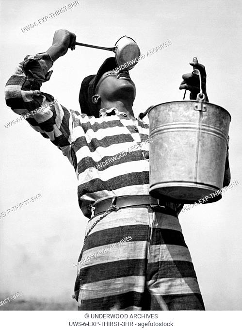 Macon, Georgia: March 8, 1937.A prisoner working on the Bibb County chain gang quenches his thirst after hours of toil on a road