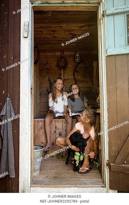 Girls playing with goat in barn